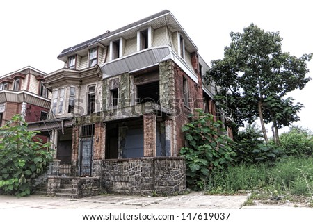 Vacant and abandoned empty boarded up house with overgrown vegetation in yard and derelict attached neighbor row home in a blight inner city urban neighborhood before rehabilitation and renewal  - stock photo