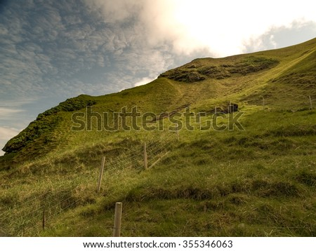 Vacant green hill pasture and bright sun with wired fence and wooden posts. Located in Heimaey, Vestmannaeyjar, Iceland. - stock photo