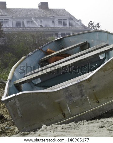 Vacant rowboat beached near house in Cape Cod on misty afternoon (selective focus) - stock photo