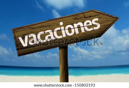 Vacanza - Vacation in Spanish - wooden sign with a beach on background  - stock photo