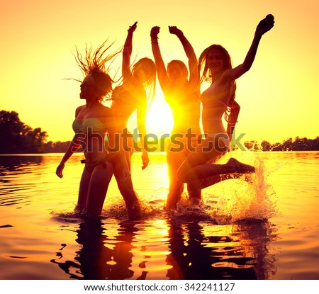 Vacation. Beach Party. Teenage girls having fun in water. Group of happy young people dancing at the beach on beautiful summer sunset. Silhouettes of group of teen girls jumping. Joyful friends - stock photo