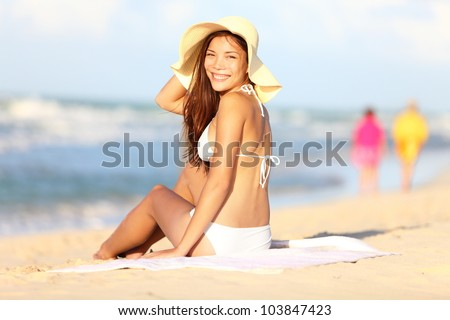 Vacation beach woman happy. Beautiful girl in bikini smiling in blissful joy at camera while sitting on beach on summer holidays travel. Pretty multiracial Caucasian / Asian Chinese model in bikini - stock photo