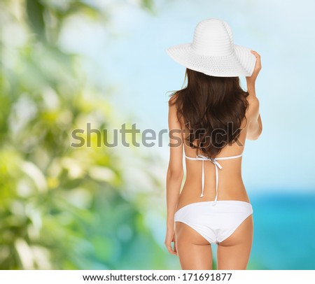 vacation, beauty and lingerie concept - back view of beautiful woman in white bikini and hat on a beach - stock photo