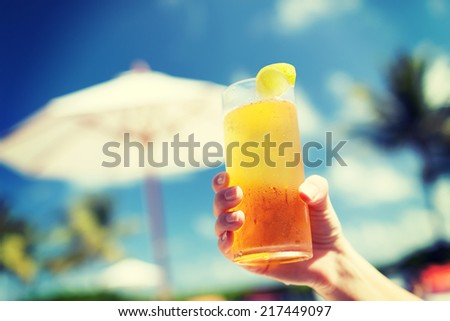 vacation, beverage and travel concept - close-up of female hand holding glass with cocktail - stock photo