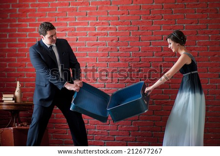 Vacation concept. groom and bride pull suitcase - stock photo
