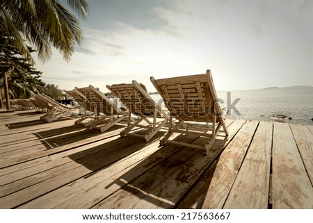 Vacation Concept. Palms and relaxing sunbeds on wooden desk near the sea under blue sky. Sepia toned - stock photo