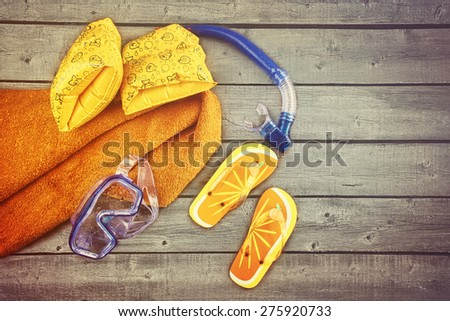 Vacation Concept. Towel and other kids beach toys on wood background - stock photo