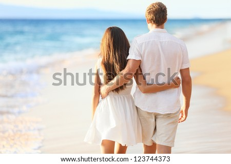 Vacation couple walking on beach together in love holding around each other. Happy interracial young couple, Asian woman and Caucasian man. - stock photo