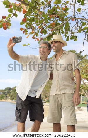 Vacation: Gay couple taking a selfie with mobile phone - stock photo