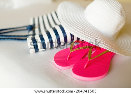 vacation, holiday and travel concept - close-up of beach bag, straw hat and flip-flops on hotel bed - stock photo