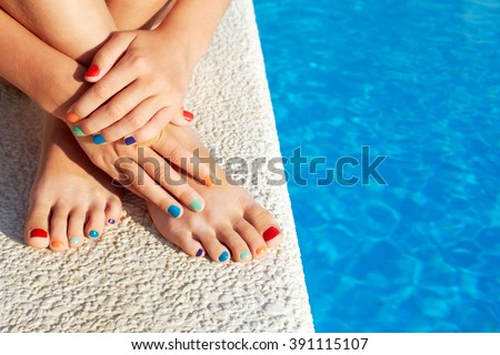 Vacation idea. Woman feet closeup. Beautiful pedicure. Girl relaxing beside swimming pool enjoying sun on sunny summer day. - stock photo