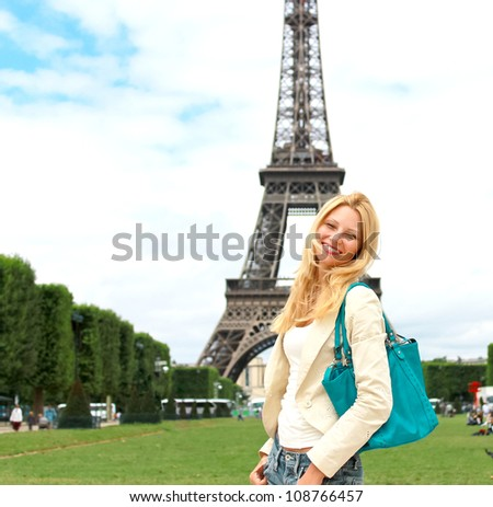 Vacation in Paris. Lucky girl near the Eiffel Tower - stock photo