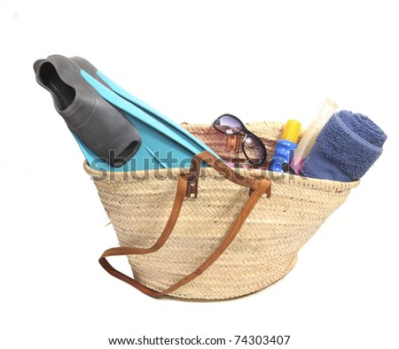 Vacation items in a wicker bag - stock photo