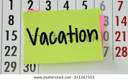 Vacation on calendar background. The phrase vacation on sticky paper note stuck to a wall calendar background - stock photo