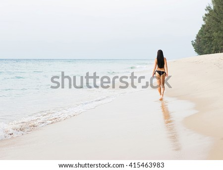 Vacation on the sea. Young sexy caucasian woman walk alone on ocean beach. Back view. - stock photo