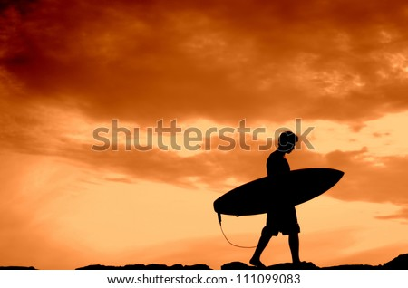 Vacation Silhouette Of A Surfer Carrying His Board Home At Sunset With Copy Space - stock photo