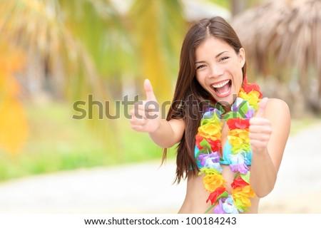 Vacation summer fun woman showing thumbs up smiling happy in joyful bliss. Pretty mixed race Asian / Caucasian female bikini model cheerful on beach. - stock photo