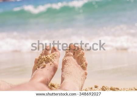 Vacation Summer Holiday,man feet on the sand beach - stock photo