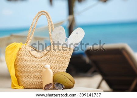 Vacation. Summer on tropical island. Straw bag, flip flops, sunglasses, sun lotion on beach background. Summer trip, traveling. Travel - stock photo