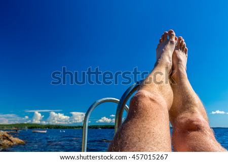 Vacation summer view - legs against water and blue sky.  - stock photo