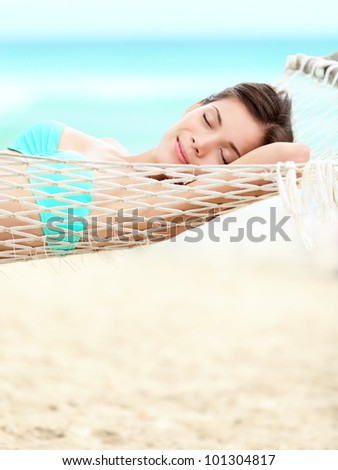 Vacation woman relaxing on beach in hammock on summer holidays resort. Beautiful happy multiracial Asian Chinese / Caucasian young woman. - stock photo