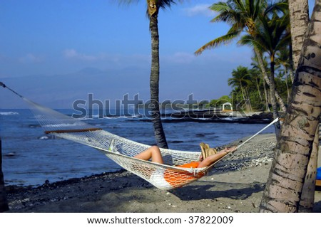 Vacationer relaxes in a hammock on the Kohala Coast.  View includes Mauna Kea mountains and the Makaiwa Bay Beach.  She is wearing a straw hat, orange shirt, white shorts and tennis shoes. - stock photo