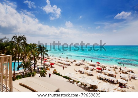 Vacationers enjoying the sun on Grand Cayman's Seven Mile Beach - stock photo