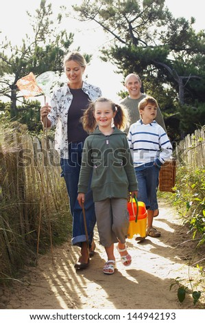 Vacationing family walking on track to beach - stock photo