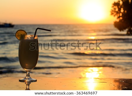 Vacations in Thaillande : backlit glass with cocktail with sunset over the sea on the background. - stock photo