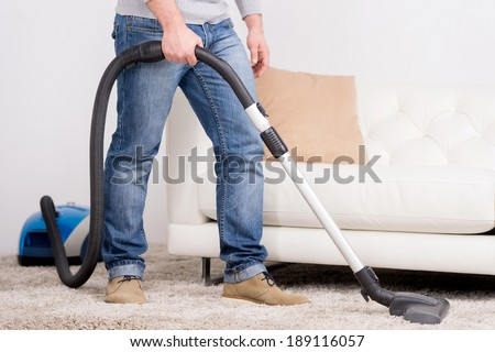 Vacuum Cleaner. A man does house work with a vacuum cleaner - stock photo