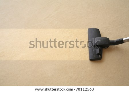 Vacuum cleaner cleans carpet, with space for text message, advertising, light yellow - stock photo