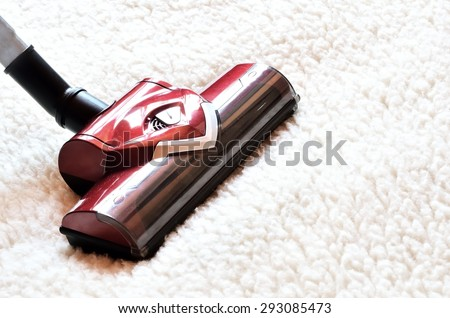 Vacuum cleaner. Close up of the head of a modern hoover being used while vacuuming a woollen furry carpet. - stock photo