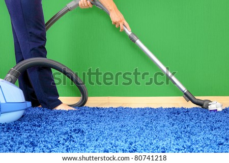 Vacuum cleaner in action  - a men cleaner a carpet. - stock photo