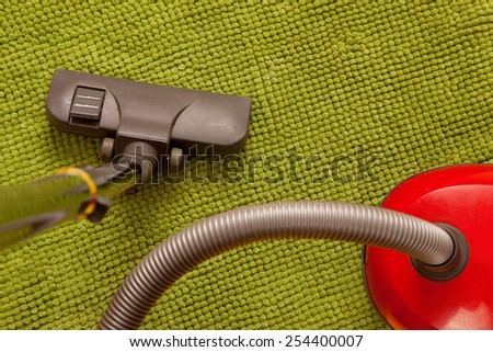 Vacuum cleaner on a green carpet. Housework - stock photo