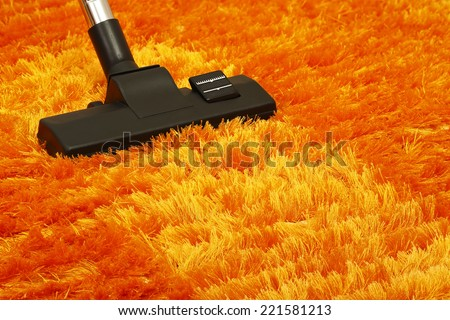 vacuum cleaner on orange fluffy carpet closeup - stock photo