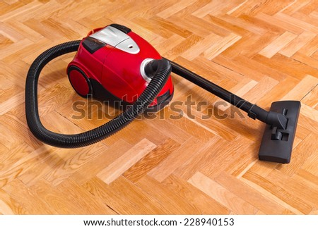 Vacuum cleaner on parquet - technology housework - stock photo