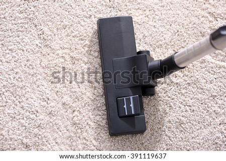 Vacuum cleaner sweeping a white carpet, close up - stock photo