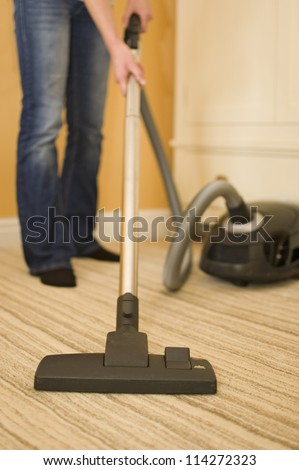 Vacuum cleaning bedroom in new house - stock photo