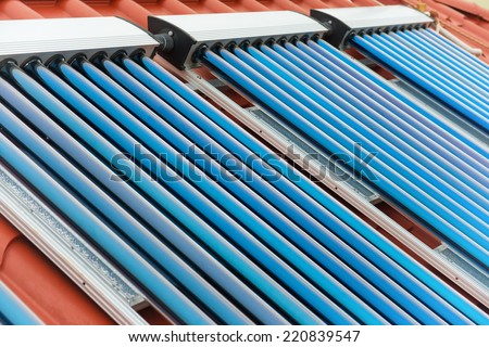 Vacuum collectors- solar water heating system on red roof of the house. - stock photo
