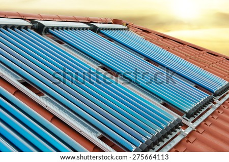 Vacuum collectors- solar water heating system on red roof of the house under shining sun - stock photo