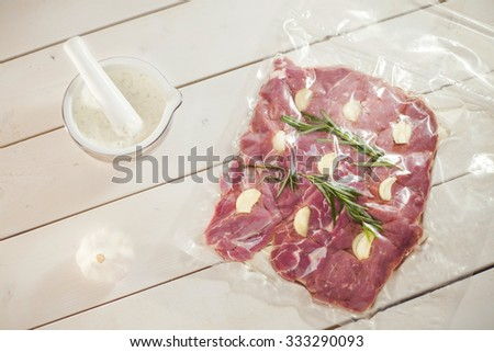 Vacuum packed lamb meat with garlic and garlic sauce on white wooden table - stock photo