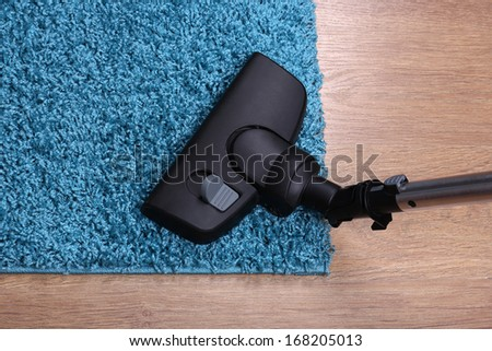 Vacuuming carpet in house - stock photo