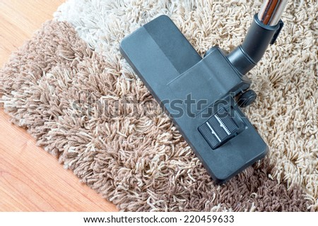 Vacuuming very dirty white carpet with cleaner - stock photo