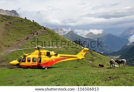 VAL DI FASSA, ITALY - AUGUST 16: Rescue helicopter from Trento Alpine Rescue Service  at accident site on August 16, 2012 in Val di Fassa, Italy - stock photo