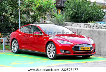 VALAIS, SWITZERLAND - AUGUST 5, 2014: Modern electric vehicle Tesla Model S in a small Alpine village. - stock photo