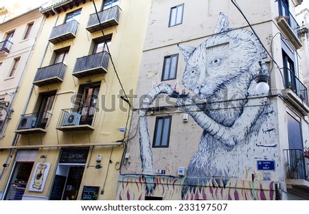 VALENCIA, SPAIN - APRIL 4 : Big garffiti painting over the facade of the building in Valencia, Spain. Painting represents a cat catching a fire on April 4th, 2014.  - stock photo