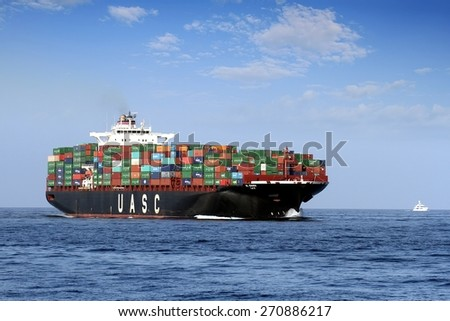"""VALENCIA, SPAIN - APRIL  17: The container ship """"UASC AL BAHIA"""" after leaving the port of Valencia is sailing in open waters, on april 17, 2015 in Valencia. - stock photo"""