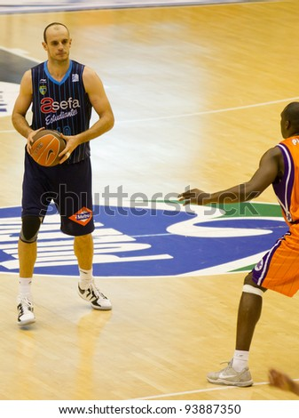 VALENCIA, SPAIN - JANUARY 28: Carlos Jimenez (blue shirt) in action during the ACB league match between Valencia Basket  and Asefa Estudiantes, 85-71, on January 28, 2012, in Valencia, Spain - stock photo