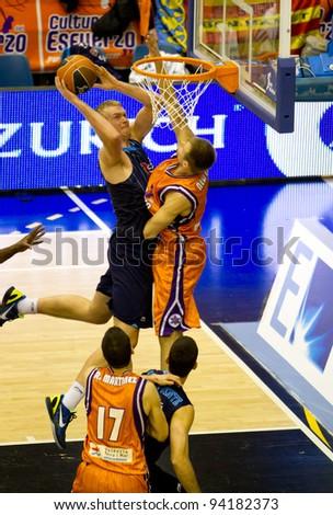 VALENCIA, SPAIN - JANUARY 28: Daniel Clark (blue shirt) slam dunk during the ACB league match between Valencia Basket  and Asefa Estudiantes, 85-71, on January 28, 2012, in Valencia, Spain - stock photo