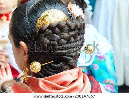 VALENCIA, SPAIN - NOVEMBER 9, 2014: traditional Valencian street party where inhabitants of all ages dance dressed in beautiful, original, handmade clothes and with typical hairstyle - stock photo